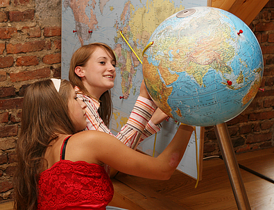 Two girls comparing a globe and a map